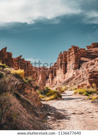 Charyn Grand Canyon with clouds and sun red orange stone Martian landscape #1136677640