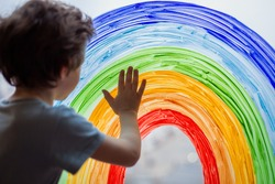 Chase the rainbow. child at home draws a rainbow on the window. Autism Awareness Day, 2 April.  quarantine pandemic coronavirus. Children create artist paints creativity vacation