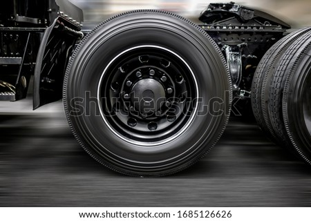 Photo of  Chassis with wheels of commercial freight transportation stylish black big rig semi truck tractor with fifth wheel hitch lubricated with grease for safe trailer transport and smooth glide