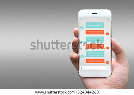 Chat bot and future marketing concept. Businessman hand holding white phone with chatbot application with gray aluminium background.