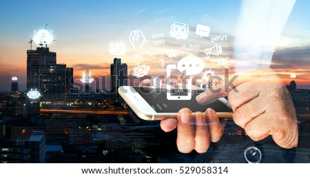 Chat bot , Robo everywhere and future marketing concept. Business woman point finger to black screen mobile phone with robot icons popup out of smartphone with metropolis city sunset background #529058314