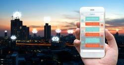 Chat bot , Robo everywhere and future marketing concept. Human hand holding white phone , application ui and robot icons with city sunset background