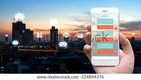 Chat bot , Robo everywhere and future marketing concept. Human hand holding white phone , application ui and robot icons with city sunset background #524844376