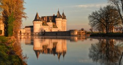 Chateau de Sully-sur-Loire in the sunset light, France. It is a famous landmark of the Loire Valley. Beautiful sunny view of the medieval castle with reflections in water. Travel and Tourism French