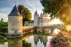 Chateau de Sully-sur-Loire in the sunset light, France. It is a famous landmark of the Loire Valley. Beautiful sunny view of the medieval castle with reflections in water. Old fortress in summer.