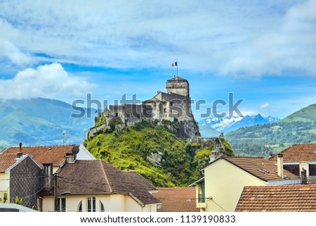 Chateau Fort of Lourdes. Castle on a rock. Snowy mountain peaks. Blue sky with white clouds. City in the Hautes-Pyrénées, France #1139190833