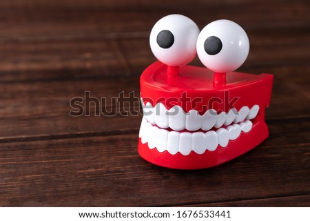Chattering teeth toy with big eyes on a wooden background with copy space. Plastic red mouth with white fangs is a concept of oral hygiene and healthy teeth Сток-фото ©