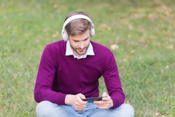 chatting time. modern life technology. mp3 player. get information from audio book. elearning concept. man listen music in headphones from smartphone. handsome guy in earphones use mobile phone.