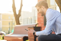 Chatting with friends. Young happy businessman wearing blue shirt and eyeglasses using smartphone and smiling while sitting on the bench on a sunny day