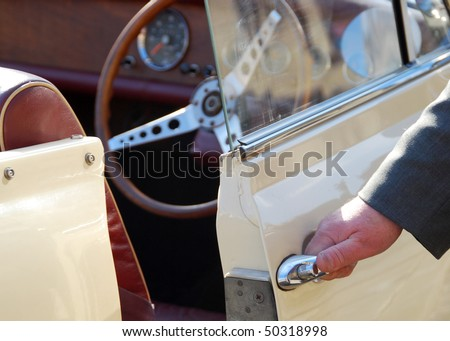 Chauffeur holds car door handle on vintage car