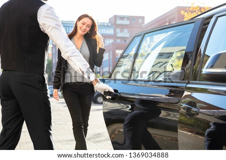 Chauffeur Opening Private Car Door For Businesswoman Foto stock ©