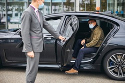 Chauffeur opening the car door for a Caucasian male passenger in a disposable face mask