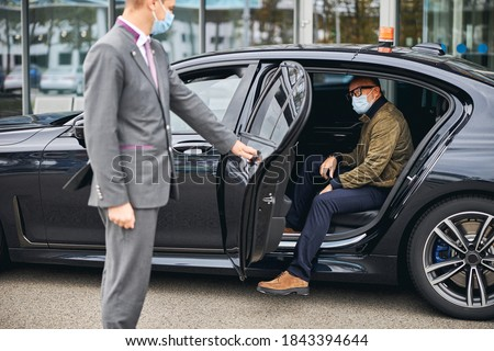 Chauffeur opening the car door for a Caucasian male passenger in a disposable face mask Stockfoto ©