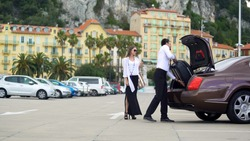 Chauffeur putting luggage in trunk, elite car service for business people