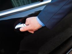 Chauffeur's hand opening passenger door on limousine