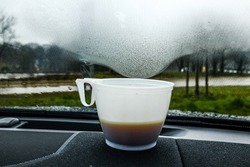Cheap coffee from a gas station giving off steam on the car window