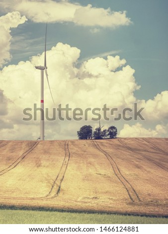 Cheap energy. Wind energy turbines in wheat field with blue sky, Renewable electric energy source, Green energy nature friendly. Wind generator on cloudy sky  #1466124881