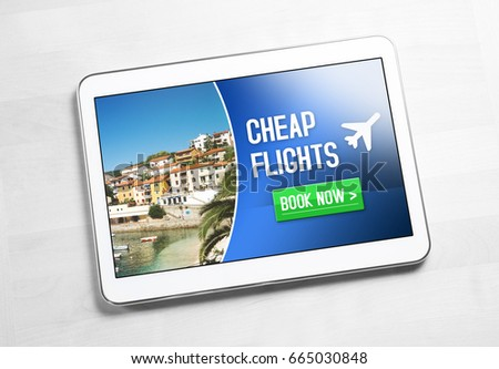 Cheap flights for sale on internet. Top view to tablet on wooden table with affordable and inexpensive vacation offer on screen. Imaginary low cost carrier application on mobile device. Book now.