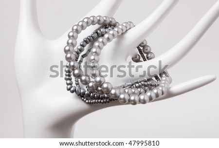Cheap plastic costume jewellery displayed on abstract hand.