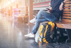 Cheap Travel and Lifestyle concept. Holiday Time, Young Traveler man wearing sneaker and sitting at train station. Asian Backpacker waiting train alone and plan trip in summer time with smart phone.