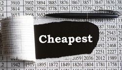 CHEAPEST is the word behind torn office paper with numbers and a black pen. Business and finance concept
