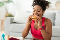 Cheat Meal. Black Fit Woman Eating Burger Enjoying Unhealthy Fast Food After Training Sitting On Floor At Home. Free Space