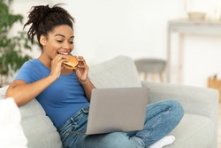 Cheat Meal. Black Woman Enjoying Unhealthy Burger Sitting At Laptop And Watching Movie At Home On Weekend. Junk Food And Dieting, Overeating Nutrition Habit Concept.