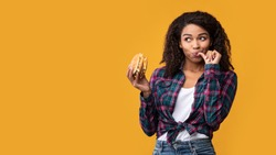 Cheat Meal. Portrait Of Happy African American Casual Woman Eating Tasty Burger, Licking Finger, Looking Away At Copy Space. Satisfied Woman Holding Fastfood, Isolated Over Orange Background, Banner