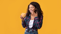Cheat Meal. Portrait Of Happy African American Lady Eating Tasty Burger, Laughing And Wiping Lips With Finger, Copy Space. Satisfied Woman Holding Fastfood, Isolated Over Orange Background, Banner