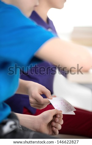 Cheating at the exam. Close up of pupils passing the paper with the right exam answers - stock photo