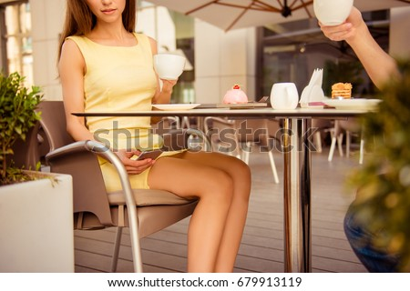 Cheating concept. Young elegant lady is texting to her lover secretly while sitting with the husband in summer terrace cafe, having brunch out #679913119