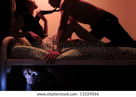 Cheating wife on bed with husband while the flirting man hides underneath
