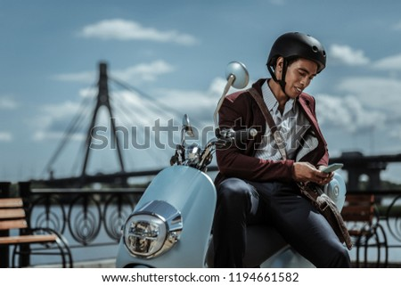 Check again. Low angle of uneasy doubtful guy leaning on motorbike and holding phone #1194661582