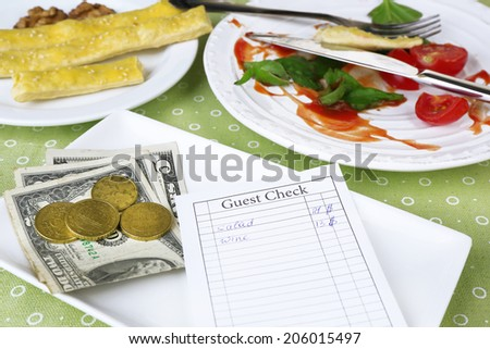 Check and remnants of food on table in restaurant