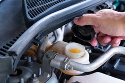 Check brake fluid,Hand open a tank for car maintenance.