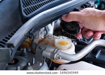 Check brake fluid,Hand open a tank for car maintenance. Foto stock ©