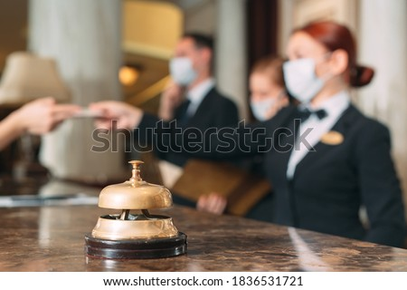 Check in hotel. receptionist at counter in hotel wearing medical masks as precaution against virus. Young woman on a business trip doing check-in at the hotel