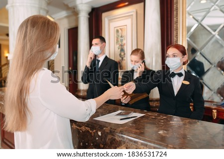 Check in hotel. receptionist at counter in hotel wearing medical masks as precaution against virus. Young woman on a business trip doing check-in at the hotel Stock foto ©