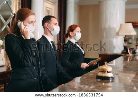 Check in hotel. receptionist at counter in hotel wearing medical masks as precaution against virus.