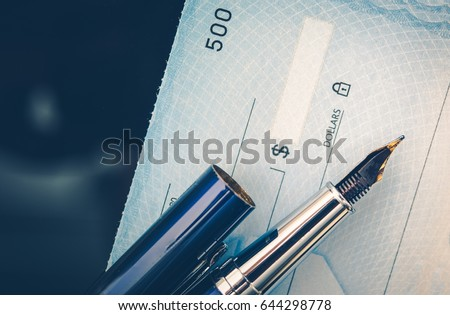 Check Issuing Concept Closeup Photo. Business Check and the Elegant Fountain Pen. Executive Desk. #644298778