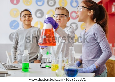 Check it out. Upbeat teenage boy lifting up a big flask and showing the ongoing reaction inside it to his classmates while they having a chemistry class in the lab together