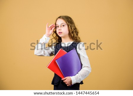 Check knowledge. Final exam coming. Girl hold textbook folder test. School exam concept. Prepare for exam. Preparing to exams in library. Small child formal wear. Formal education and homeschooling. #1447445654