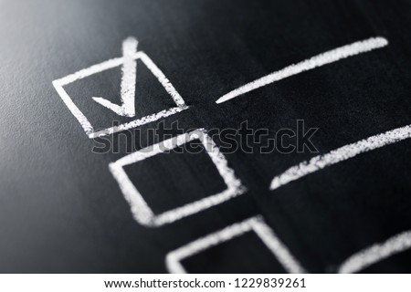 Check list on blackboard macro close up. Document of finished work duties and responsibilities. Agenda and progress in business. Checklist, keeping score of obligations or completed tasks in project.