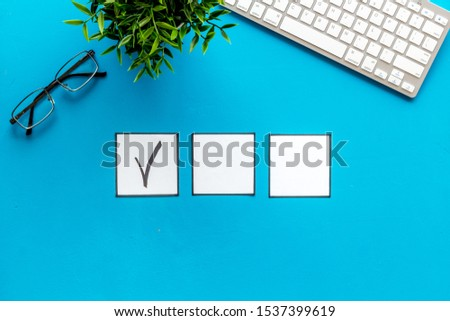 Check mark in check-box of check list on blue office background top view copy space #1537399619