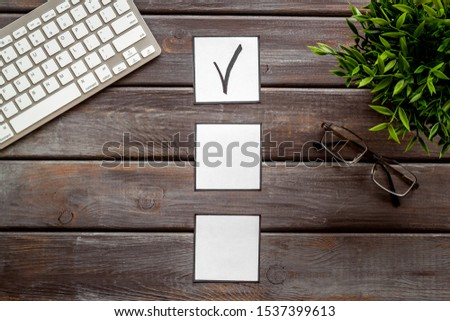 Check mark in check-box of check list on dark wooden office background top view copy space #1537399613