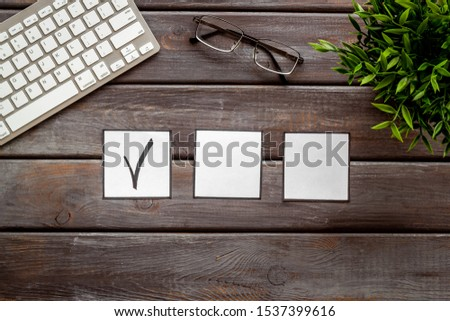 Check mark in check-box of check list on dark wooden office background top view copy space #1537399616