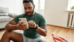Check results. Young man using smartphone app while having morning workout at home. Freshman relaxing after training. Online personal trainer on mobile phone. Focus on face. Web Banner
