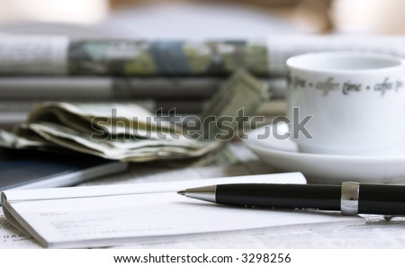 check with pen, coffee and money with newspapers on background
