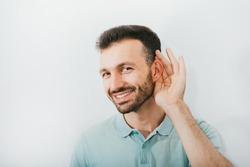 Check your hearing. Positive man holds his hand near his ear, on a gray background. Ear health, treatment and diagnosis of hearing