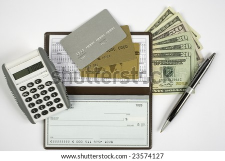 Checkbook open with blank check showing along with a calculator, pen, cash, and credit cards.